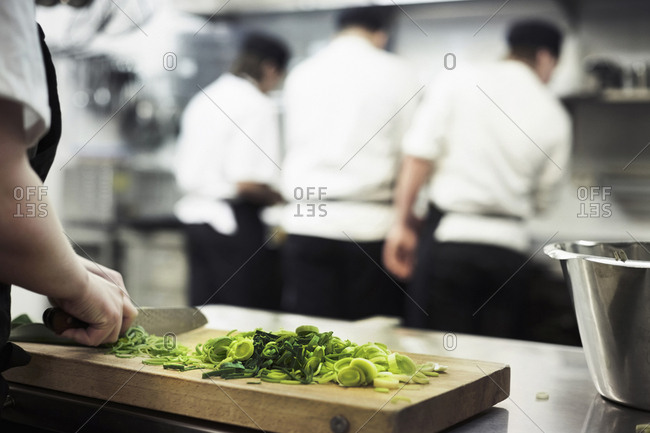 Cropped image of female chef chopping leek on cutting board with colleagues in background at restaurant