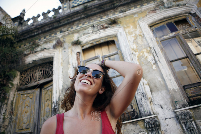 Smiling woman by abandoned building, Brazil