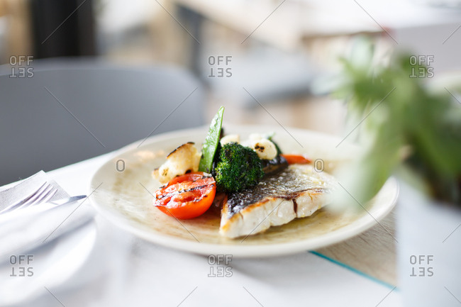 Cooked white fish served with grilled vegetables