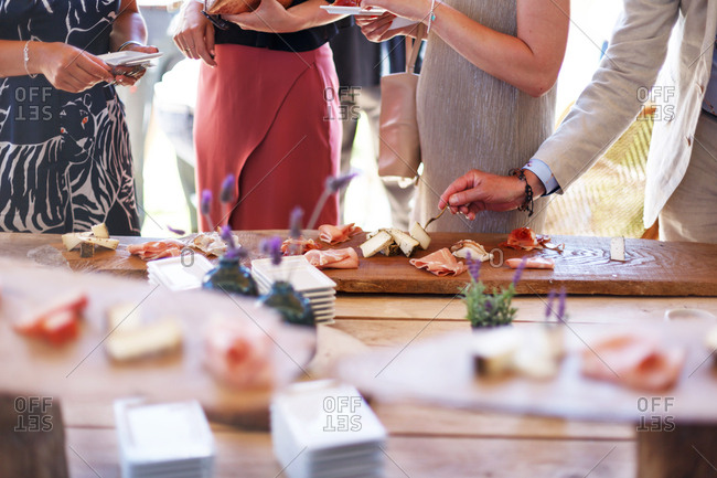 People choosing from a variety of meats and cheeses on serving board