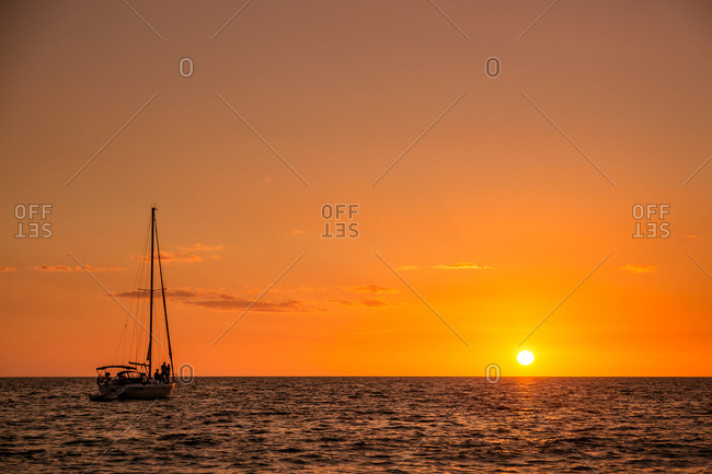 Ocean view with a sailboat and sunset low on the horizon