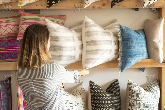 Rear view of female interior designer adjusting cushions on shelves in retail studio