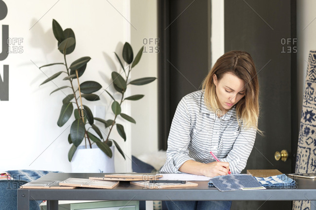 Female interior designer drawing designs at desk in retail studio