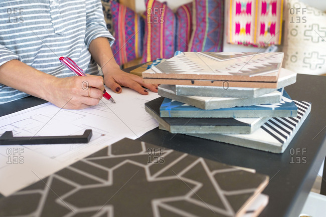 Mid section of female interior designer drawing designs at desk in retail studio