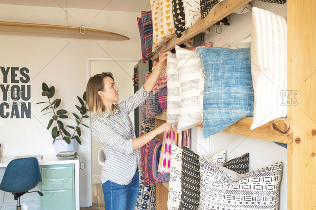 Female interior designer adjusting cushions on shelves in retail studio