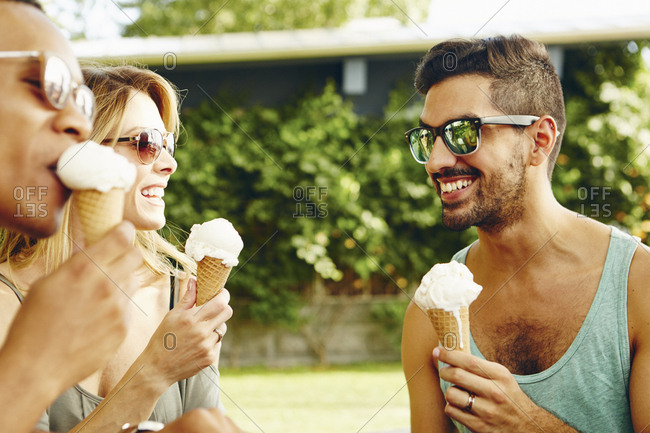 Male and female friends eating ice cream cones in park