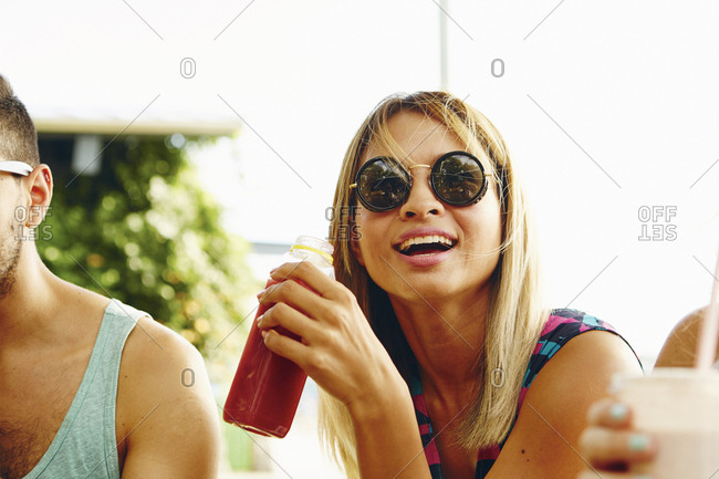 Male and female friends relaxing with drinks in park