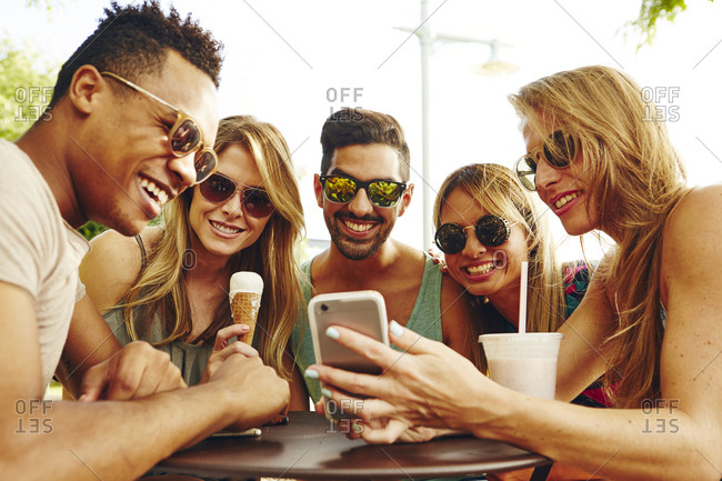 Five adult friends looking at smartphone at park table