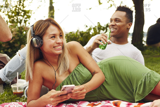 Woman choosing smartphone music while picnicking in park