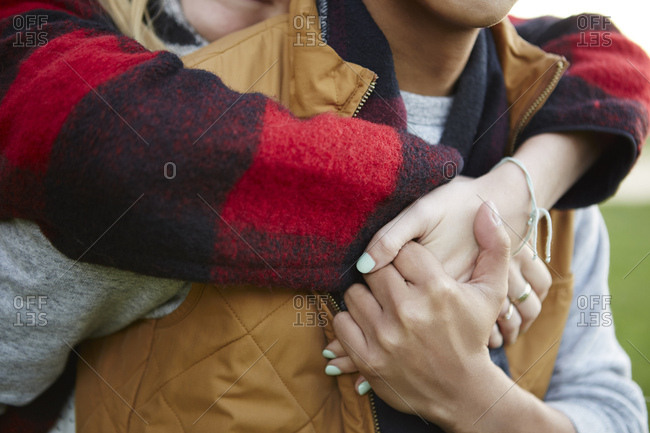 Cropped close up of woman hugging and holding boyfriend's hands