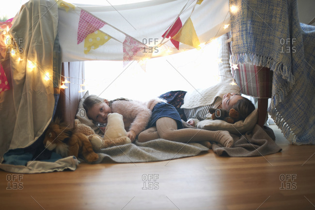 Two sisters in bedroom den lying down with soft toys