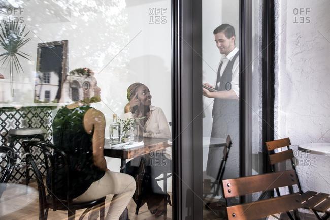 Waiter serving diners in restaurant