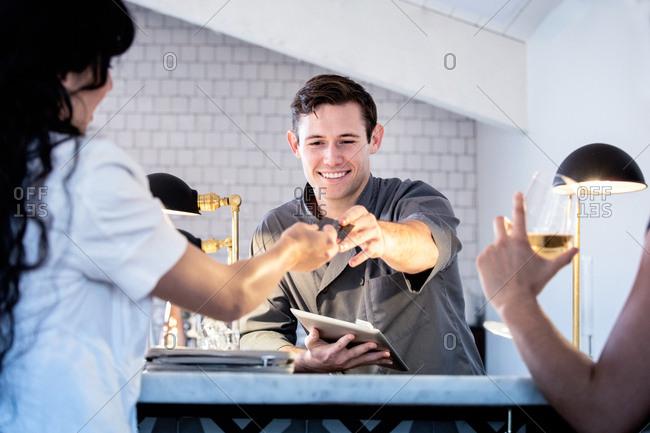 Barman serving customers at bar, barman using digital tablet to take payment