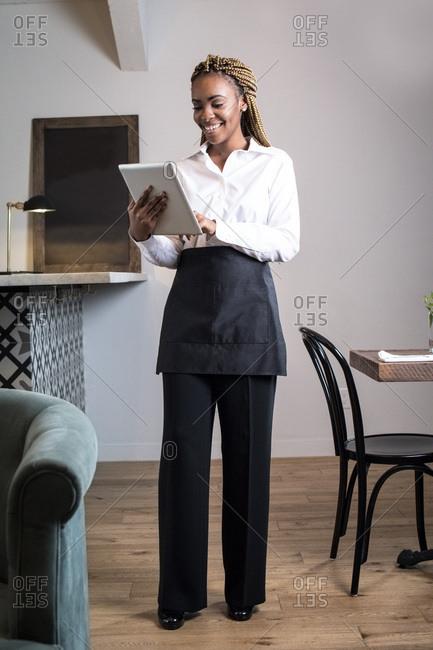 Portrait of waiter in restaurant, using digital tablet