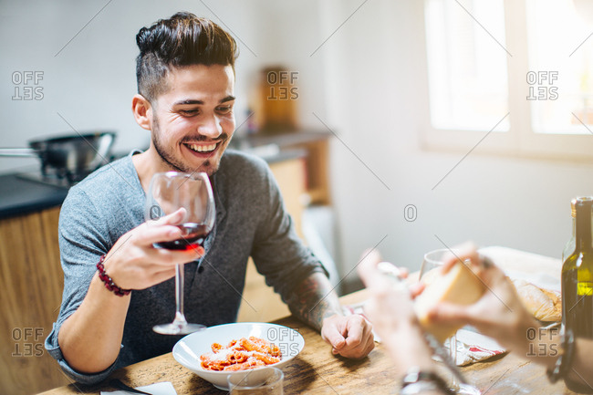 Male couple enjoying meal together, grating parmesan cheese on pasta, drinking wine