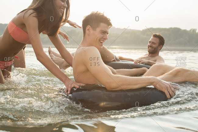 Friends having fun with inflatable ring in river