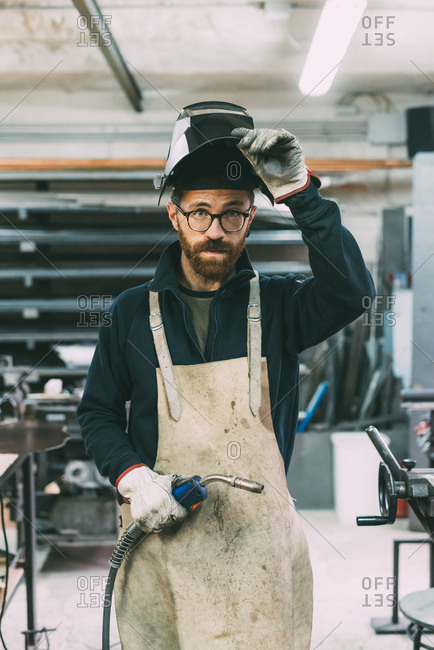 Portrait of metalworker holding welding torch in forge workshop