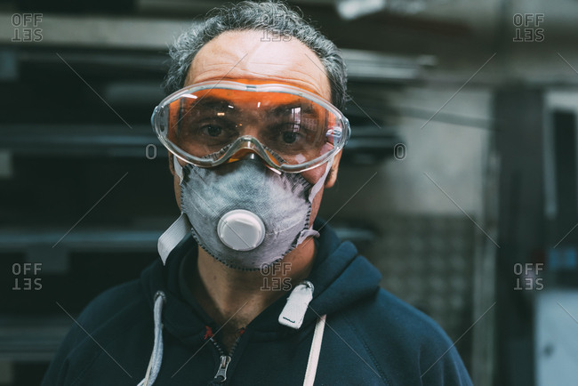 Portrait of metalworker in dust mask and safety goggles in forge workshop