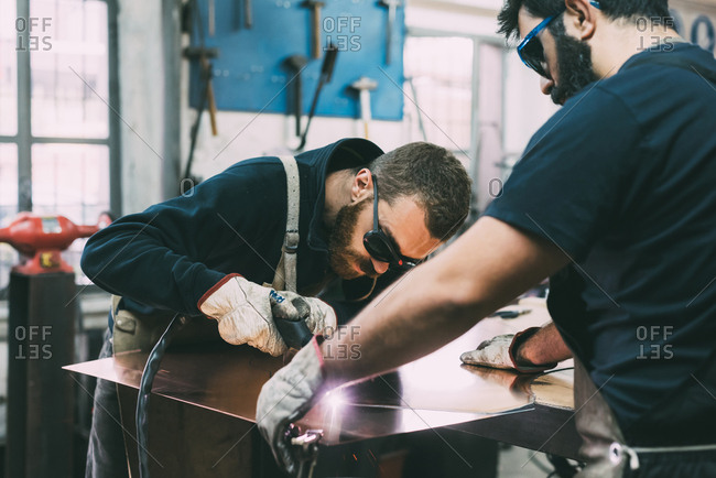 Metalwork team cutting copper with welding torch in forge workshop