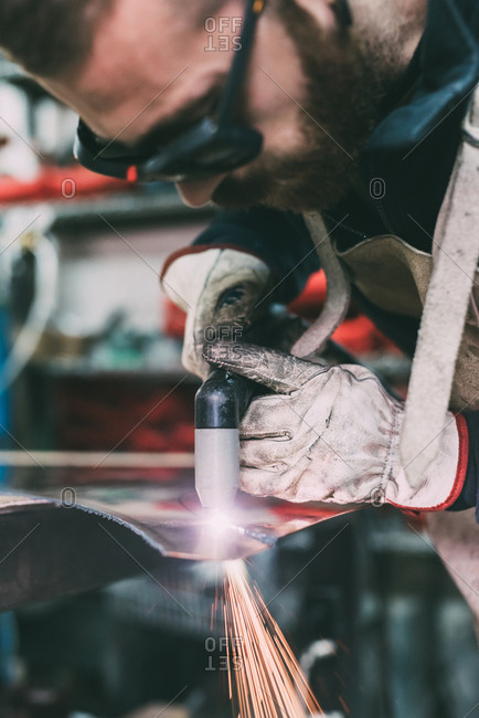 Metalworker cutting copper with welding torch in forge workshop