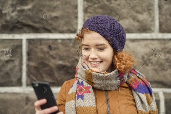 Woman outdoors, using smartphone, smiling