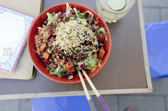 Overhead view of vegetarian salad with noodles on sidewalk cafe table