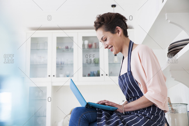 Young female baker sitting on kitchen counter typing on laptop