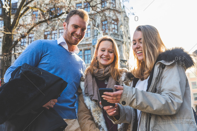 Young man and female friends looking at smartphone in city street