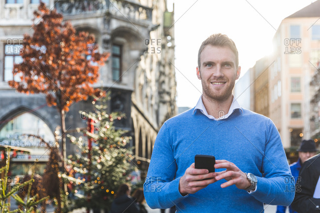 Portrait of young man holding smartphone at Christmas market