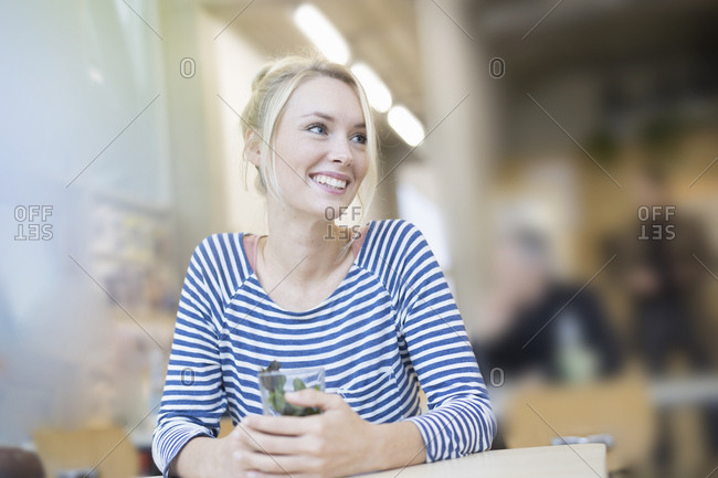 Young woman alone in cafe with herbal tea
