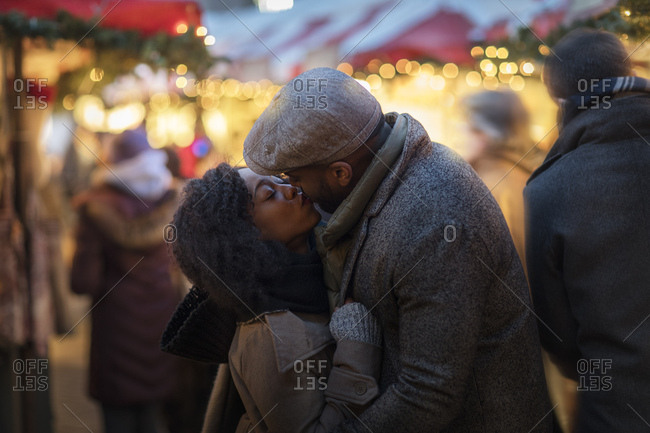 Romantic couple kissing at Christmas market, New York, USA