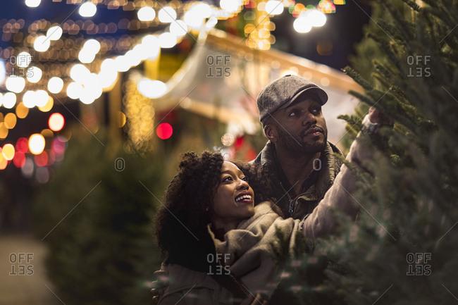 Couple selecting Christmas tree at Christmas market at night, New York, USA