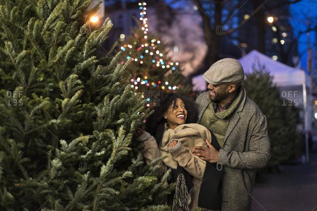 Couple choosing Christmas tree at night, New York, USA