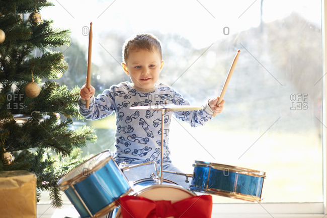 Boy playing toy drum kit on Christmas day