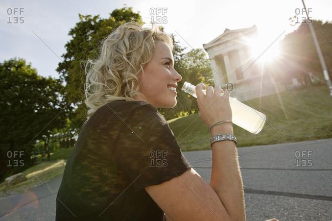 Mid adult woman in sunlit park drinking lemonade