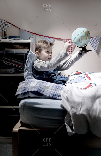 Boy sitting up in bed pointing while holding up globe