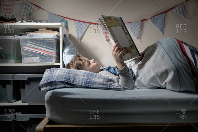 Boy lying in bed reading book