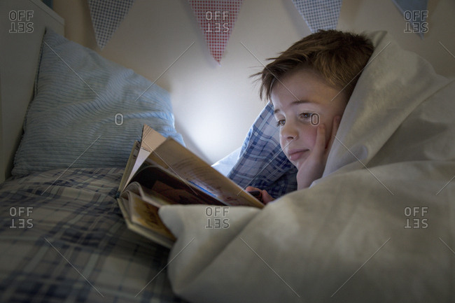 Boy lying in bed wrapped in duvet reading book