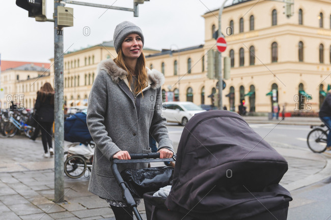 Mid adult woman crossing city road with baby carriage