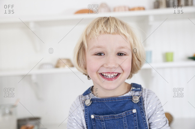 Portrait of happy cute girl with blond bob in kitchen