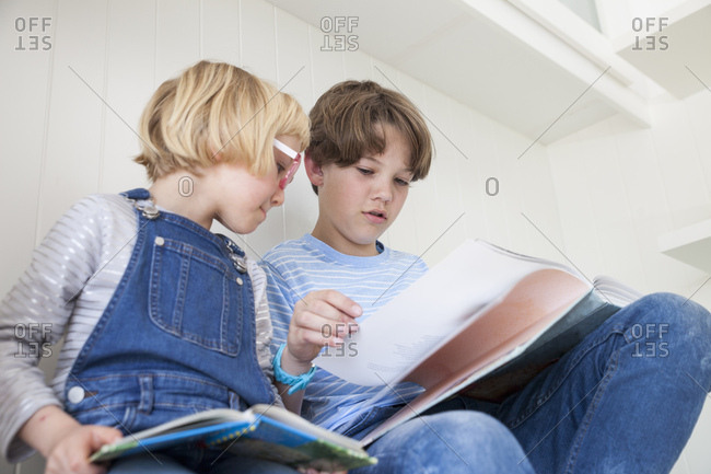 Girl reading storybook with brother on kitchen counter