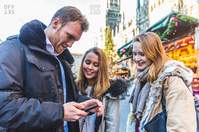 Young man and female friends looking at smartphone at Christmas market
