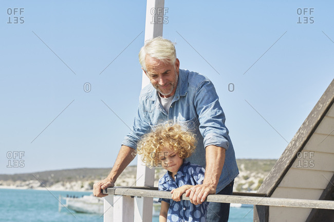 Grandfather and grandson on houseboat deck, Kraalbaai, South Africa