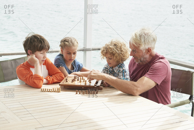 Grandfather and grandchildren playing chess