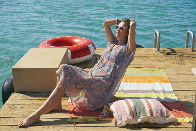 Woman sunbathing on houseboat sun deck, Kraalbaai, South Africa