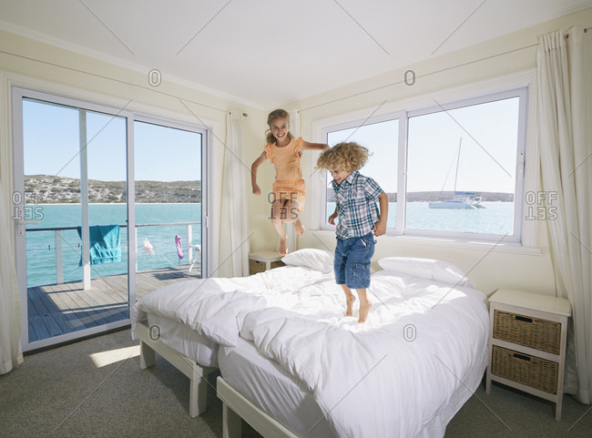 Boy and girl jumping on bed in houseboat, Kraalbaai, South Africa