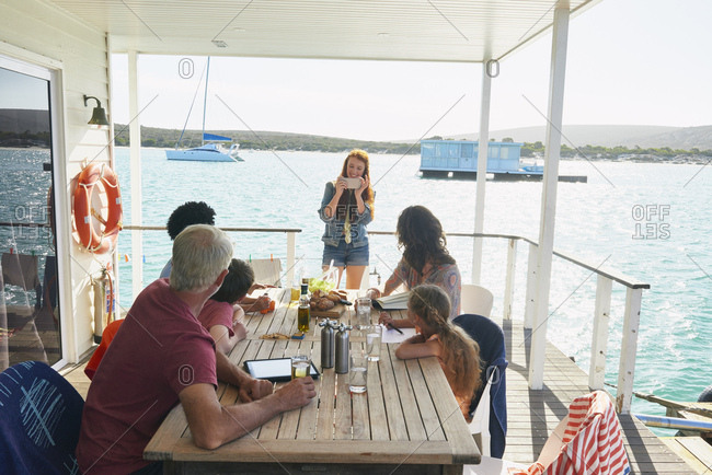 Family gathered at table on houseboat sun deck, Kraalbaai, South Africa
