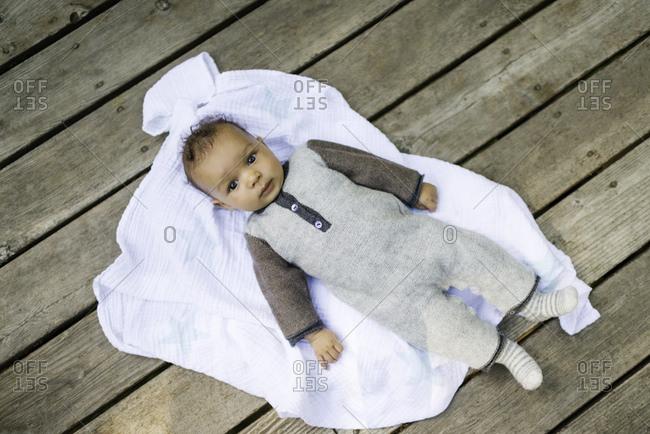 Portrait of baby boy lying on blanket, overhead view