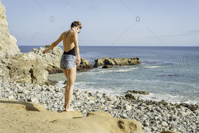 Young woman standing on rocks at beach, rear view