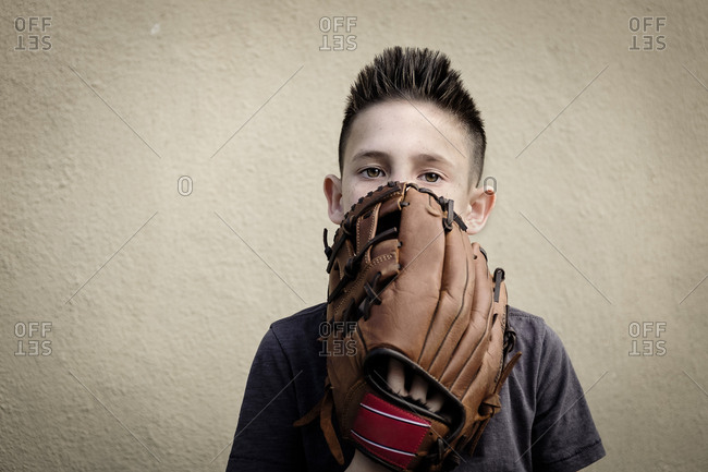 Boy covering mouth with baseball glove
